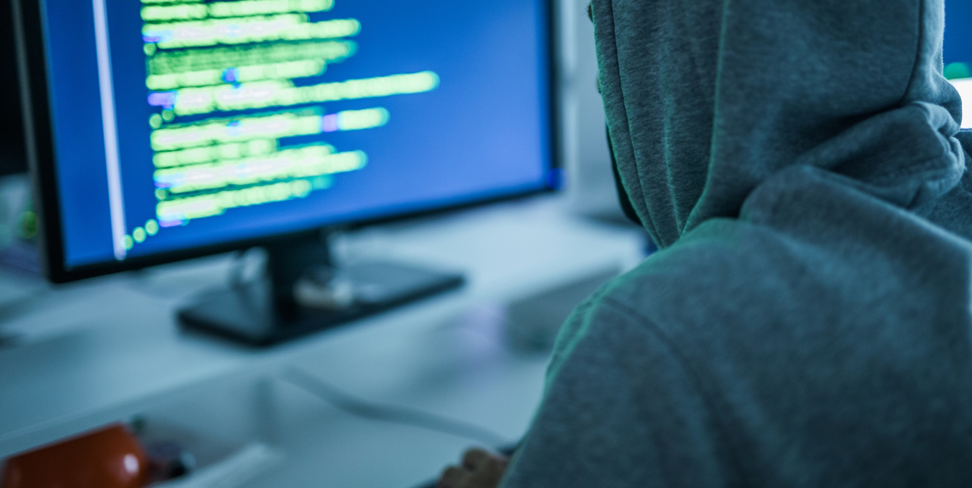 A computer hacker sat in front of a screen