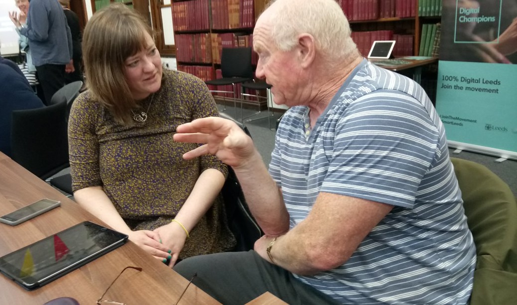 Two people in a library, with the woman talking to an older man, and an iPad on the table in front of them