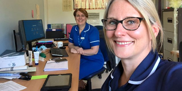 Photo of digital midwives Lorri Allport and Petra Maclening in uniform sitting in an office.