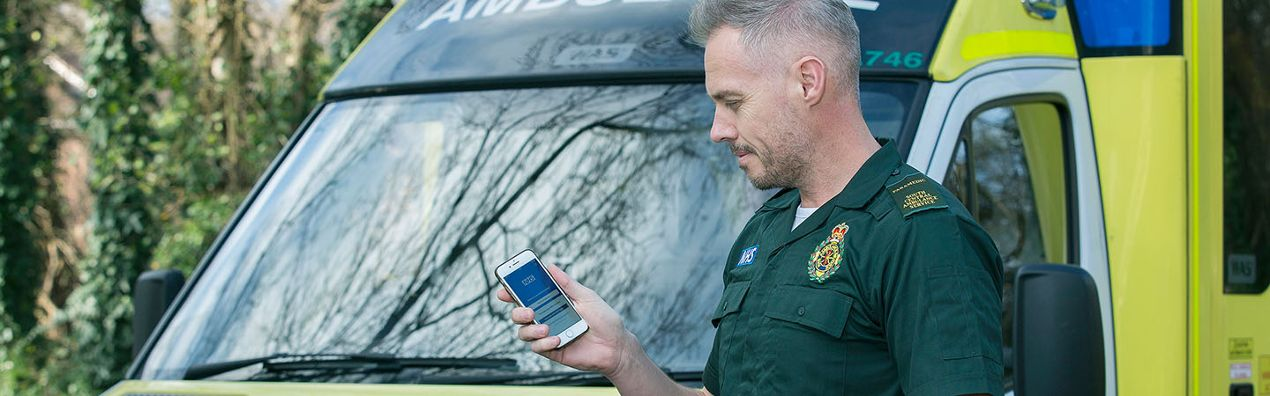 Paramedic looks at app on phone, in front of ambulance