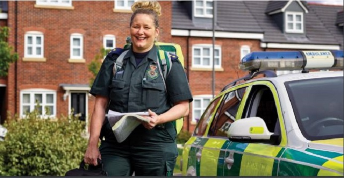 A female paramedic exiting a rapid response vehicle, carrying a rucksack, bag and paperwork