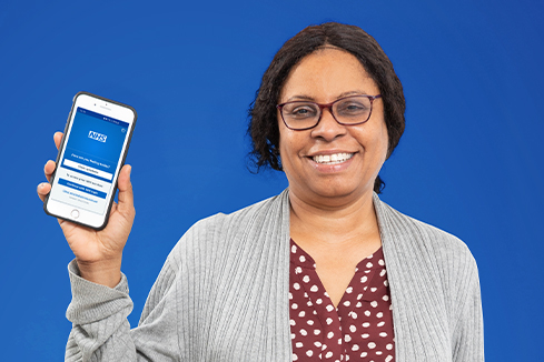 Dionne holding a phone with the NHS App open