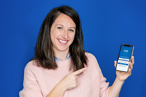 Harriet holding a phone with the NHS App open