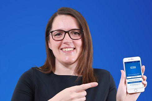 Sarah holding a phone with the NHS App open