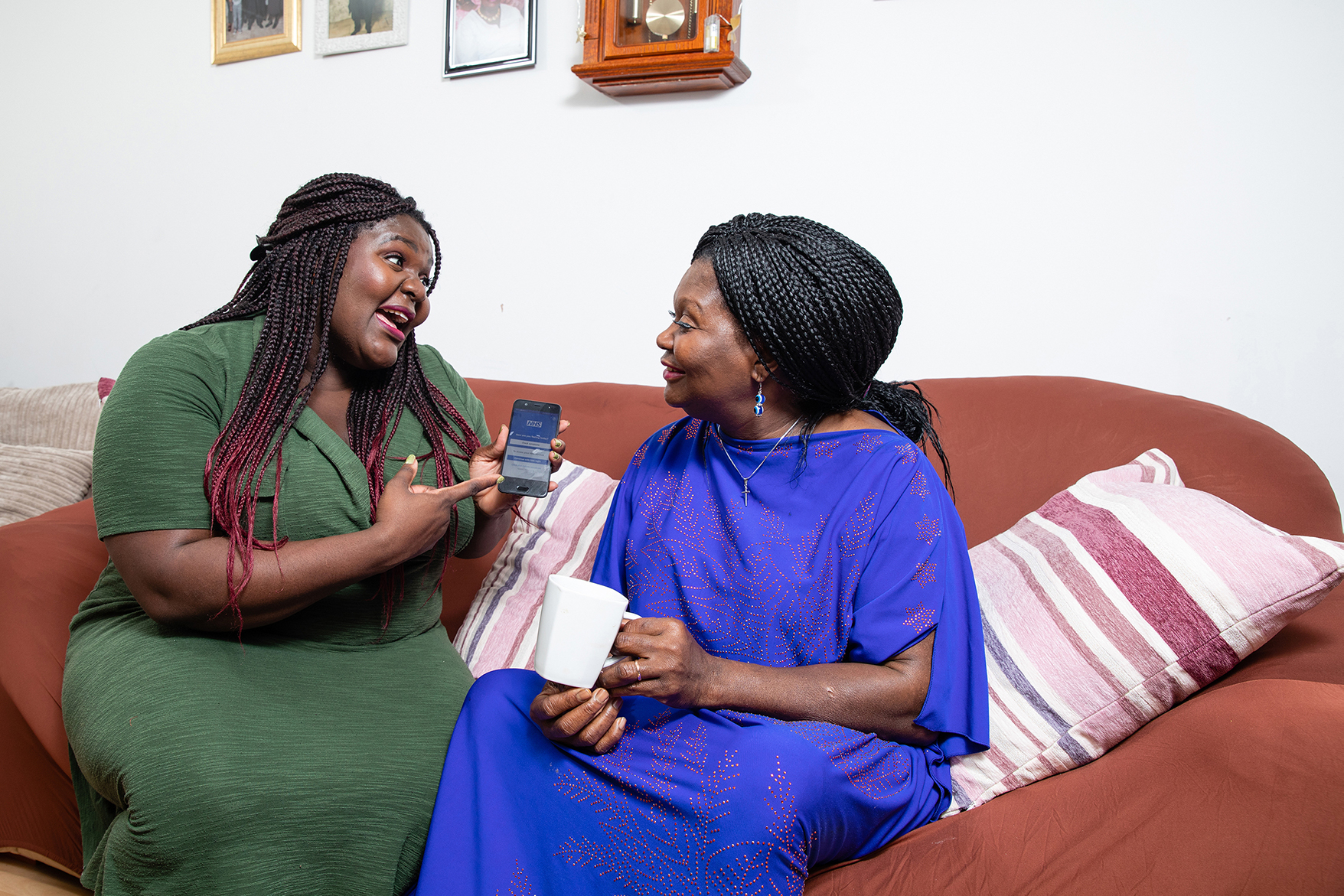 Elizabeth sitting on a sofa, showing her Mum Esther the NHS App
