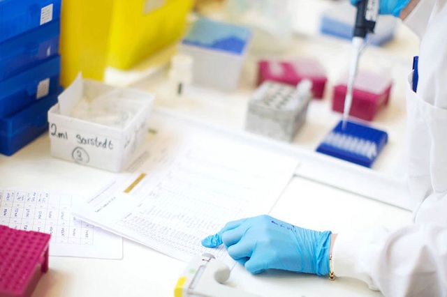 Image of a laboratory worker checking notes whilst operating a pipette