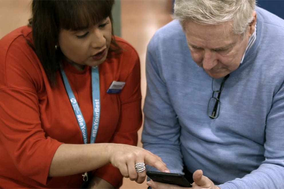 Member of NHS staff assisting a person with their mobile phone