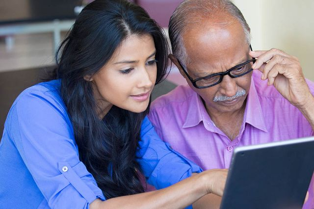 A young female assists an older man to use an ipad