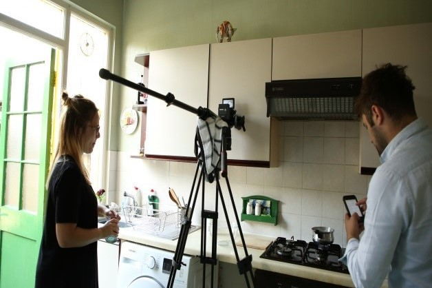 Woman filming with a smartphone on tripod in a kitchen