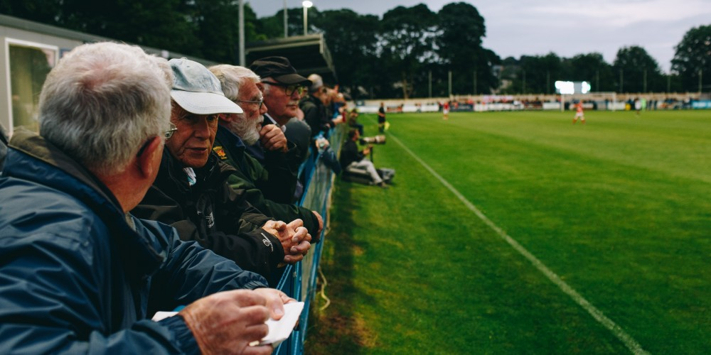 Some men in their 60s or 70s standing watching a non-league football match