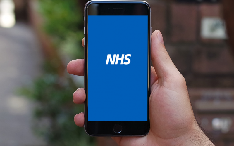 A hand holding a smart phone displaying an NHS logo on a plain blue background